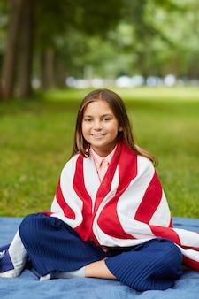 Retrato de corpo inteiro vertical de uma linda garota coberta pela bandeira americana, sentado na manta de piquenique no parque e sorrindo