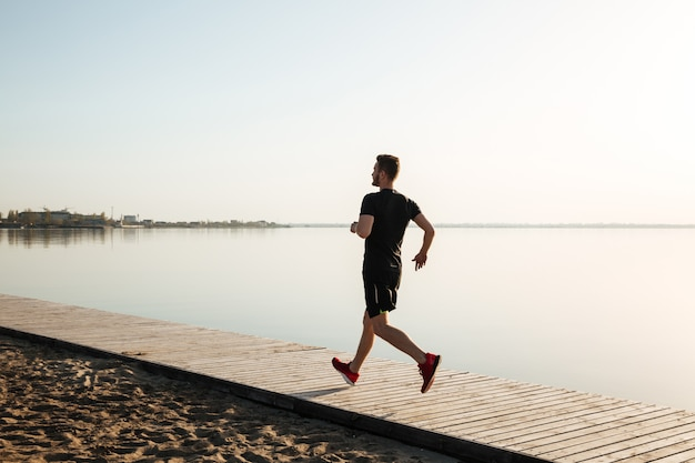 Retrato de corpo inteiro vista traseira de um desportista saudável correndo
