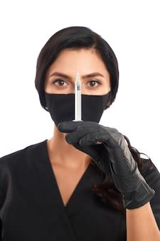 Retrato de cosmetologista qualificado com máscara médica preta, uniforme e luvas preparando seringa para procedimentos de beleza