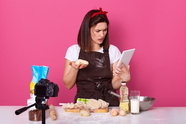 Retrato de cozinhar amador segurando a massa em uma mão e tablet