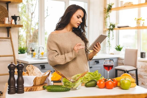 Retrato de cozinhar comida jovem saudável na cozinha, procurando uma receita na internet. usando computador tablet.
