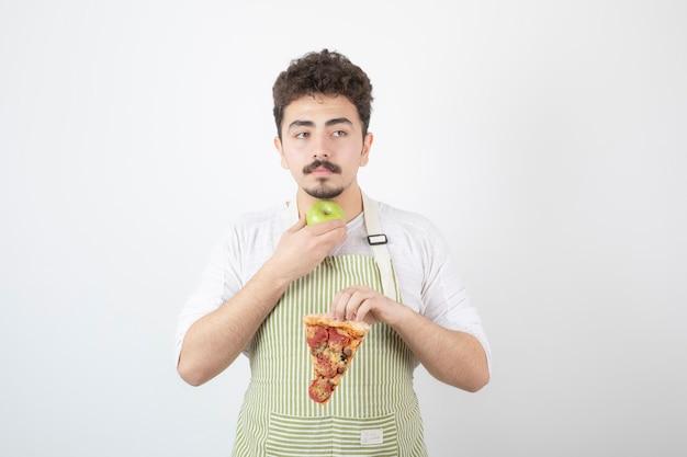 Retrato de cozinheiro masculino segurando pizza e maçã verde em branco