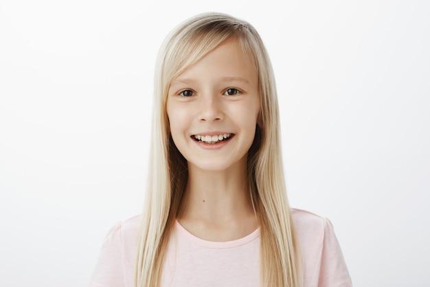 Retrato de criança adorável despreocupada e amigável com cabelos loiros, sorrindo amplamente e expressando atitude positiva, desfrutando de um ótimo dia nas aulas de teatro