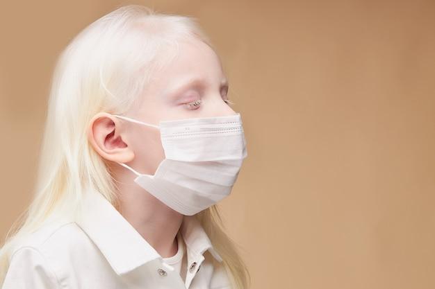 Retrato de criança albina mística e doente com máscara médica isolada