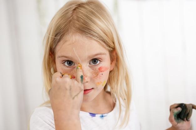 Retrato de criança angelical com manchas coloridas de tinta no rosto