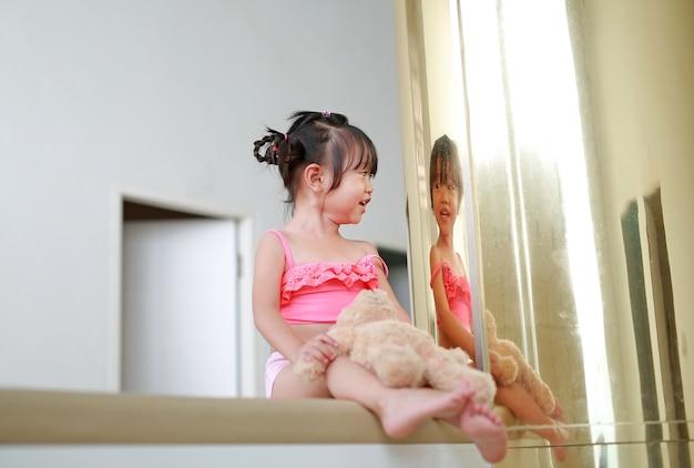 Retrato, de, criança asian, menina, em, terno natação, mentindo, ligado, sofá, com, reflexão, polaco