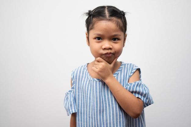 Retrato de criança asiática de 5 anos e para pentear o cabelo e colocar as mãos no queixo e fazer pose pensativa
