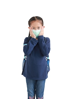 Retrato de criança asiática em uniforme escolar usando máscara médica isolada.