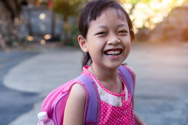 Retrato de criança asiática sorridente feliz menina com mochila