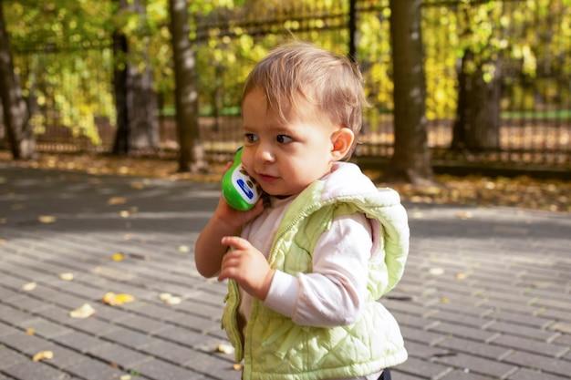 Retrato de criança bonita brincando, falando em um telefone de brinquedo.