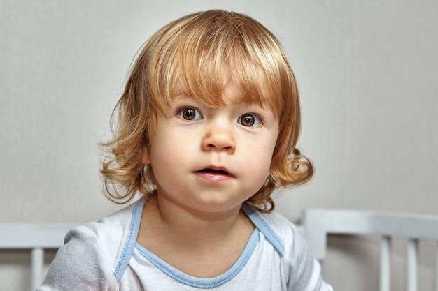 Retrato de criança branca encantadora branca com cabelo loiro encaracolado.