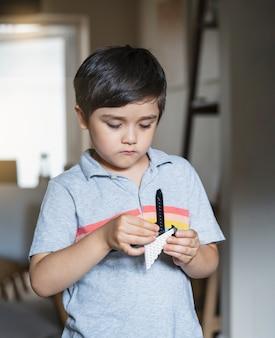 Retrato de criança brincando com blocos de plástico, criança em pé na sala de estar concentrada em seus brinquedos