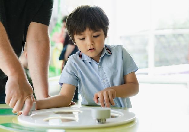 Retrato de criança brincando na sala de jogos com os pais, pai e filho