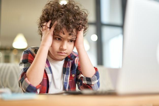 Retrato de criança cansada de menino latino cansado segurando sua cabeça e parecendo triste enquanto estudava