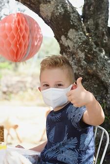 Retrato de criança com máscara dando aprovação com o polegar da mão