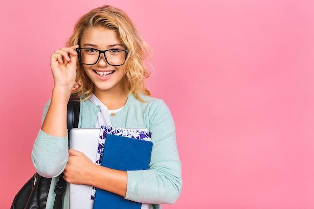 Retrato de criança de criança de escola sorridente com bolsa escola, laptop e livros, conceito de educação.
