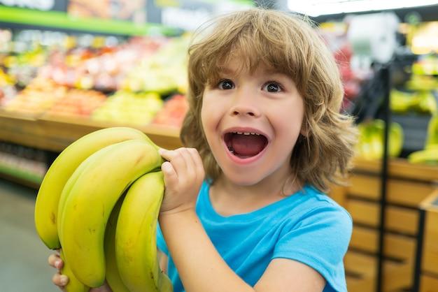 Retrato de criança em compras de supermercado no supermercado criança comprando banana fresca no supermercado