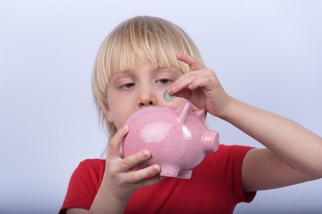 Retrato de criança em fundo branco com cofrinho na mão. rapaz coloca moedas no cofrinho.