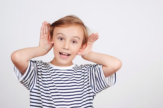 Retrato de criança engraçada ouve algo. menino bonito segura a mão perto da orelha. comunicação familiar com criança.