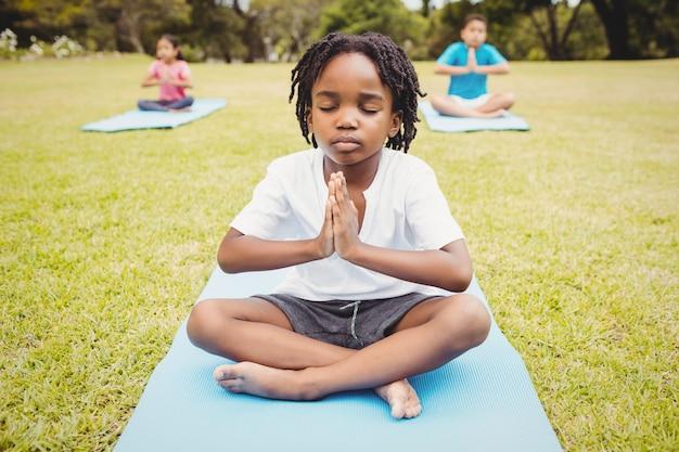Retrato de criança fazendo yoga com amigos