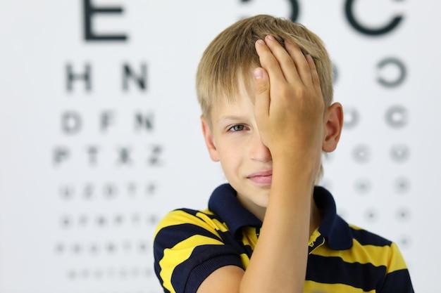 Retrato de criança fechando um olho com criança de mão na consulta com o oftalmologista no quadro da clínica