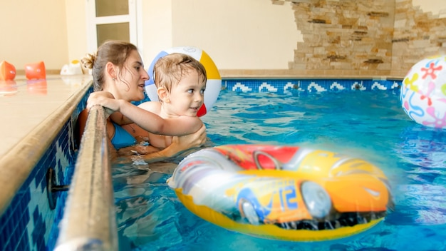 Retrato de criança feliz e sorridente brincando com uma bola de praia colorida inflável com a mãe na piscina interna