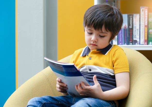 Retrato de criança infeliz sentado sozinho olhando para o livro com o rosto entediado na biblioteca, menino chateado chile com cara triste com profundo através de sentado sozinho na livraria, menino com rosto entediado