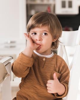 Retrato de criança lambendo os dedos