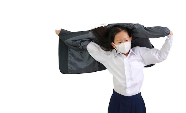 Retrato de criança menina asiática em camisa branca com máscara protetora levanta a mão para tirar o terno formal de estudante isolado no fundo branco. imagem com caminho de recorte