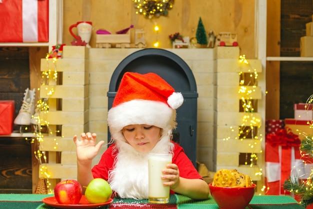 Retrato de criança papai noel bebendo leite de vidro e segurando biscoitos.