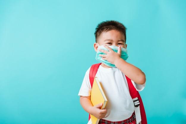 Retrato de criança pequena asiática menino jardim de infância usar máscara protetora e saco de escola segurar livro antes de ir para a escola