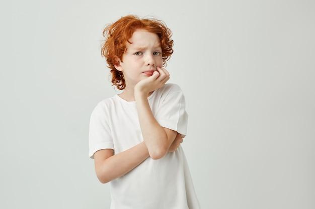 Retrato de criança pequena bonita com cabelo ruivo e sardas, segurando a cabeça com a mão, pensando nos trabalhos de casa, ele precisa fazer até a noite.