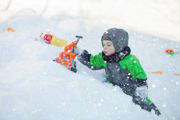 Retrato de criança pequena bonito sentado na neve e brincando com seu brinquedo trator amarelo no parque. criança brincando ao ar livre