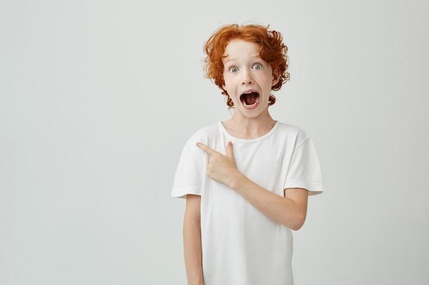 Retrato de criança ruiva alegre com sardas posando com a boca aberta e expressão louca, apontando para copyspace