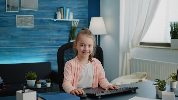 Retrato de criança sentada à mesa com o computador para aulas online