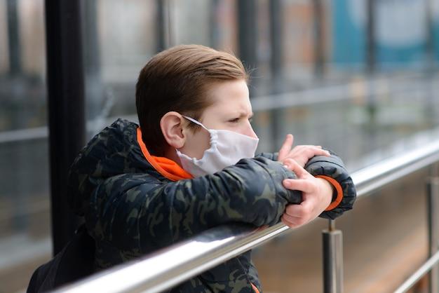 Retrato de criança triste caucasiana em máscara facial no parque fechado ao ar livre.
