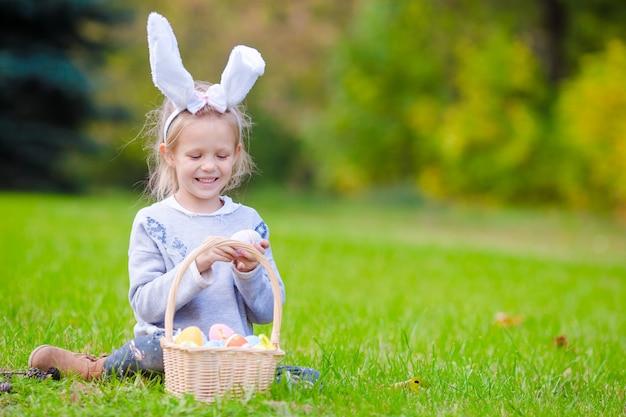 Retrato de criança usando orelhas de coelho com uma cesta cheia de ovos de páscoa na primavera ao ar livre