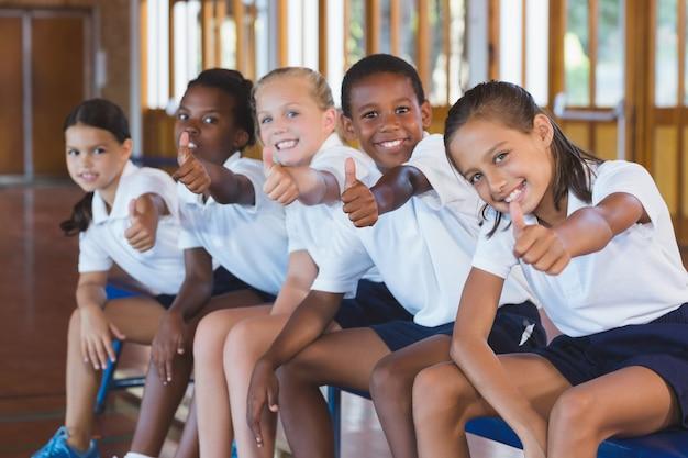 Retrato de crianças da escola aparecendo polegares na quadra de basquete