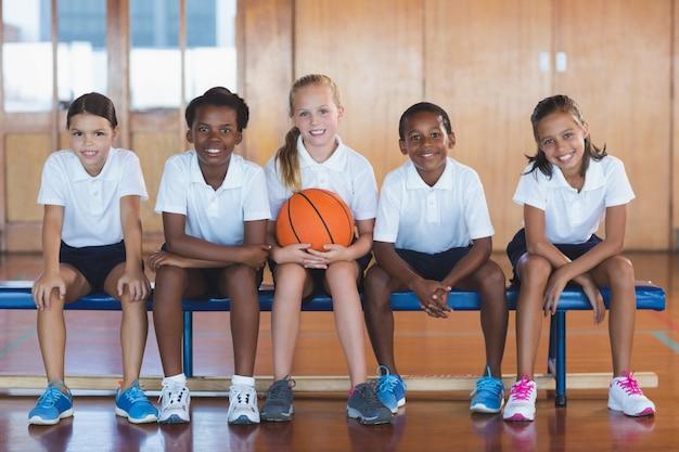 Retrato de crianças da escola sentado na quadra de basquete