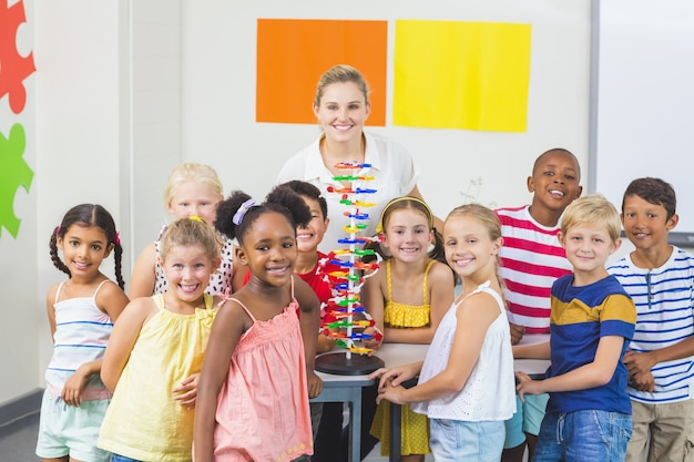 Retrato de crianças e professor em pé no laboratório