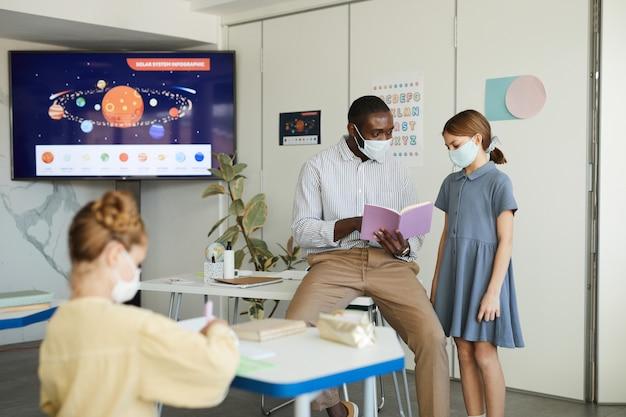 Retrato de crianças e professores usando máscaras na sala de aula, medidas de segurança ambiciosas, espaço de cópia