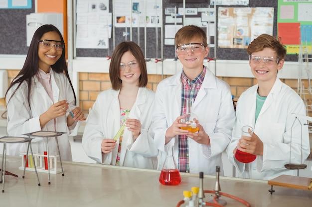 Retrato de crianças em idade escolar fazendo um experimento químico em laboratório