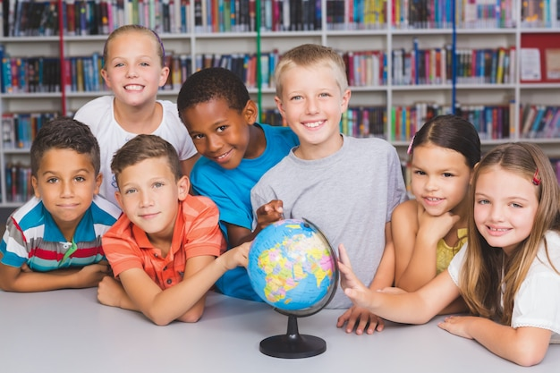 Retrato de crianças em idade escolar, olhando para o globo na biblioteca