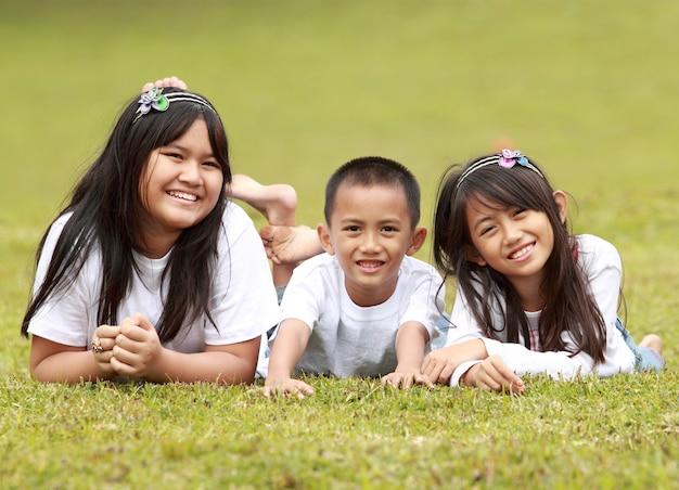 Retrato de crianças felizes, deitado na grama