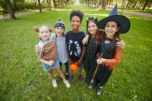 Retrato de crianças felizes em fantasias de halloween, abraçando-se e sorrindo para a câmera em pé no parque
