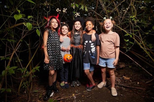 Retrato de crianças felizes em fantasias de halloween em pé na floresta escura e sorrindo para a câmera