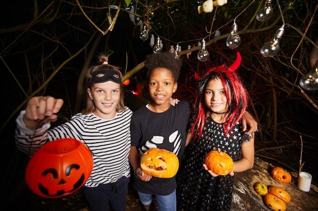 Retrato de crianças felizes em fantasias de halloween segurando abóboras e sorrindo para a câmera em pé no escuro
