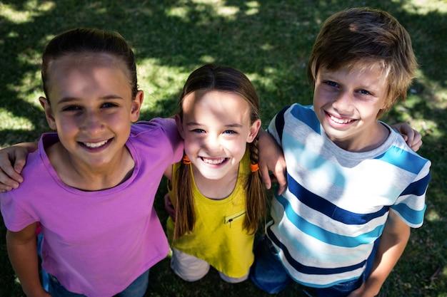 Retrato de crianças felizes em pé no parque