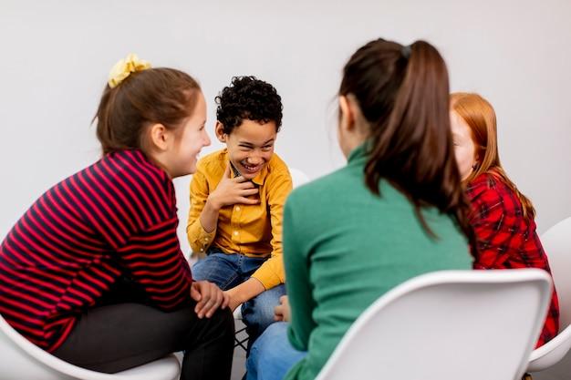 Retrato de crianças fofas em jeans conversando e sentando em cadeiras contra a parede branca