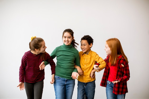 Retrato de crianças fofas em jeans conversando e sorrindo, caminhando contra a parede branca